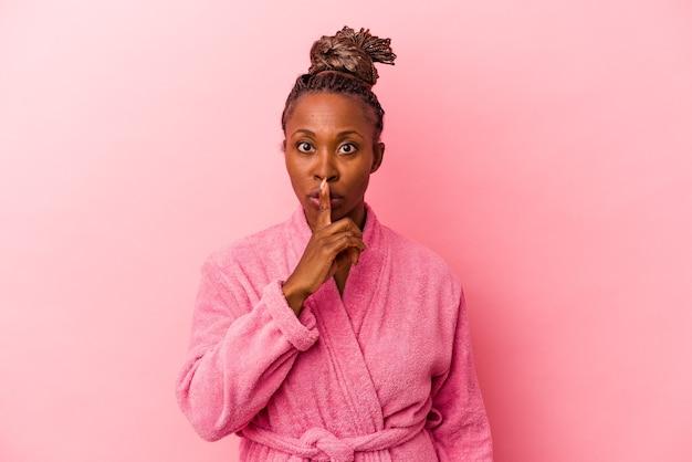 Jonge afrikaanse amerikaanse vrouw die roze badjas draagt die op roze achtergrond wordt geïsoleerd die een geheim houdt of om stilte vraagt.