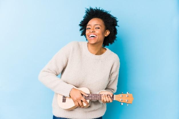 Jonge afrikaanse amerikaanse vrouw die ukelele speelt