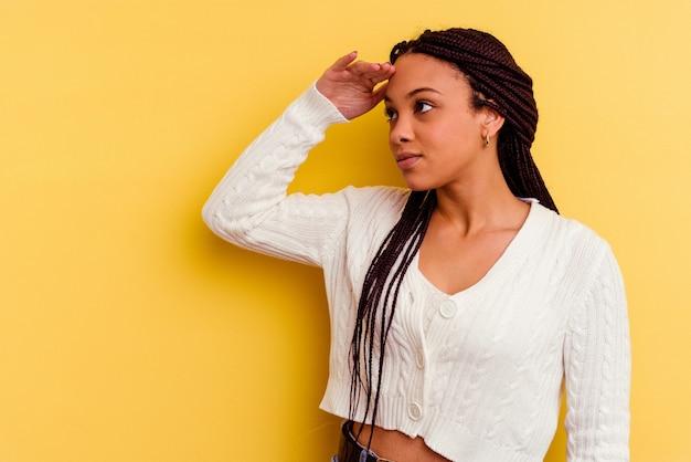 Jonge afrikaanse amerikaanse vrouw die ver weg kijkt die hand op voorhoofd houdt.