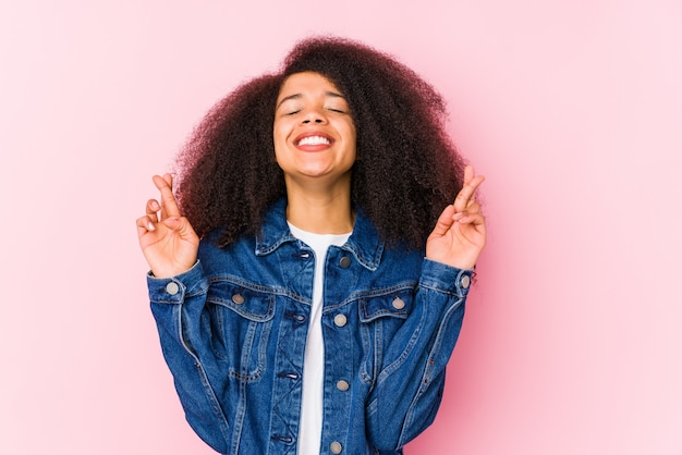 Jonge afrikaanse amerikaanse vrouw die vingers kruist voor het hebben van geluk