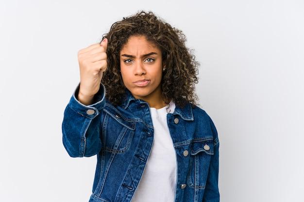 Jonge afrikaanse amerikaanse vrouw die vuist, agressieve gezichtsuitdrukking toont.