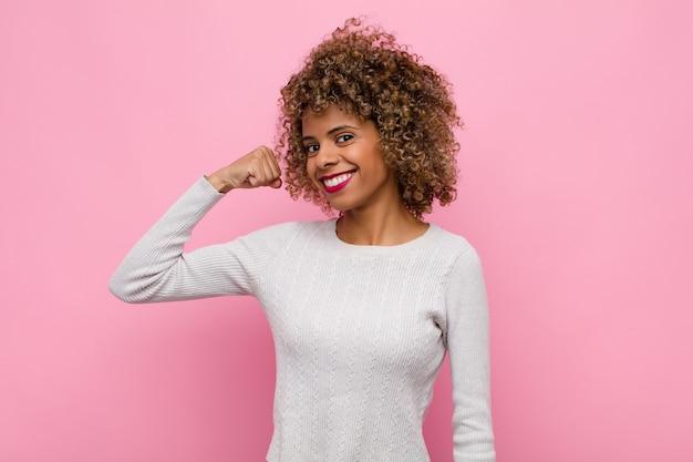 Jonge afrikaanse amerikaanse vrouw die zich gelukkig, tevreden en krachtig voelt, buigende geschikte en gespierde biceps, die sterk voor de gymnastiek zorgen tegen roze muur