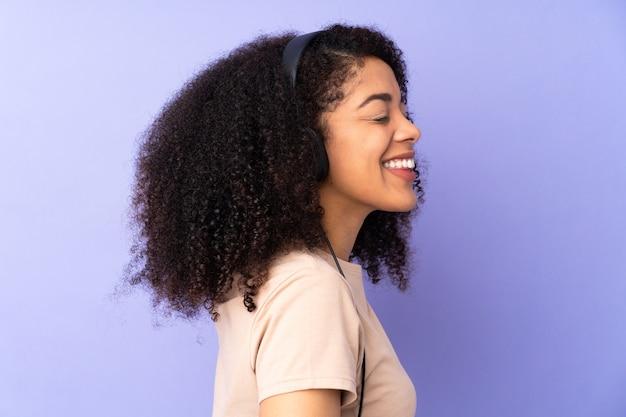 Jonge afrikaanse amerikaanse vrouw geïsoleerd luisteren muziek en dansen