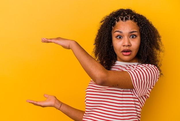 Jonge afrikaanse amerikaanse vrouw geïsoleerd op gele muur geschokt en verbaasd met een kopie ruimte tussen handen.