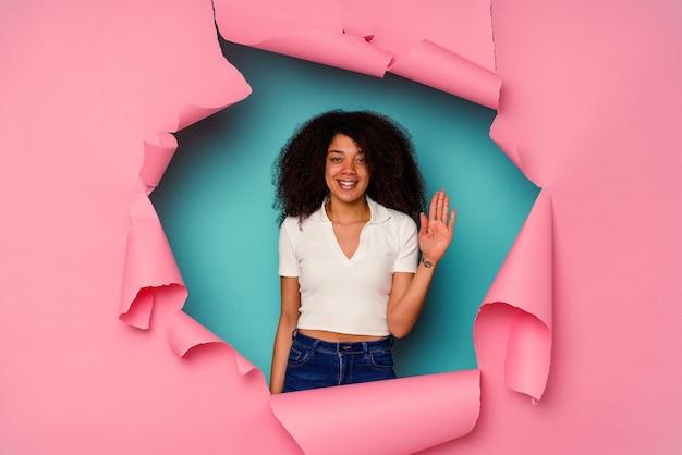 Jonge afrikaanse amerikaanse vrouw in gescheurd document dat op blauwe achtergrond wordt geïsoleerd die vrolijk glimlachen toont nummer vijf met vingers.