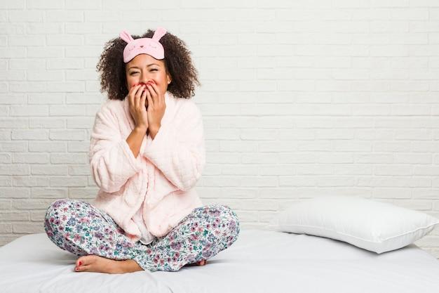 Jonge afrikaanse amerikaanse vrouw in het bed dat pijama draagt die om iets lacht, die mond behandelt met handen.