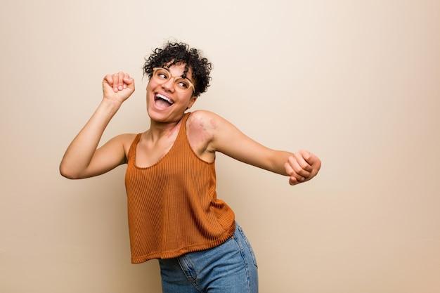 Jonge afrikaanse amerikaanse vrouw met huidgeboorteteken die en pret dansen hebben