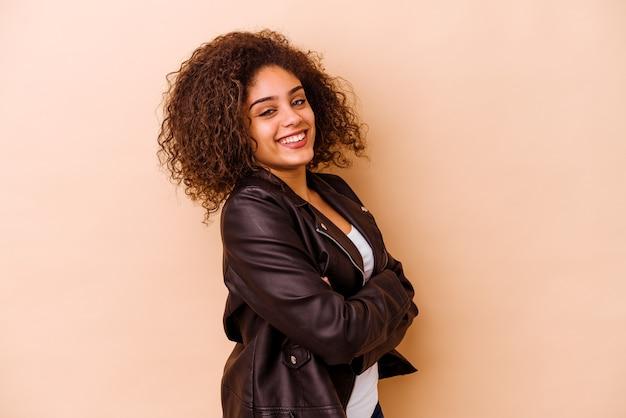 Jonge afrikaanse amerikaanse vrouw op beige gelukkig, glimlachend en vrolijk.