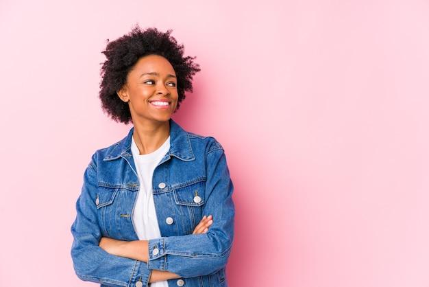 Jonge afrikaanse amerikaanse vrouw op roze backgroound geïsoleerd glimlachend zelfverzekerd met gekruiste armen.