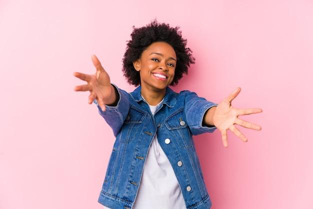 Jonge afrikaanse amerikaanse vrouw tegen een geïsoleerde roze muur voelt zich zelfverzekerd door een knuffel te geven