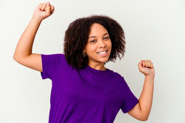 Jonge afrikaanse amerikaanse vrouw van gemengd ras geïsoleerd viert een speciale dag, springt en heft wapens met energie op.