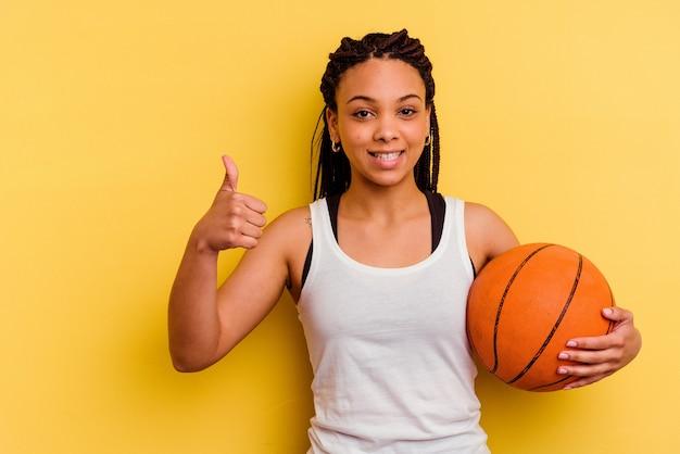 Jonge afrikaanse amerikaanse vrouwen speelbasketbal dat op gele achtergrond wordt geïsoleerd die en duim glimlacht opheft