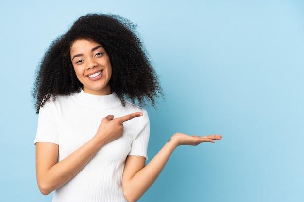 Jonge afrikaanse amerikaanse vrouwenholding denkbeeldige copyspace op de palm om een advertentie in te voegen