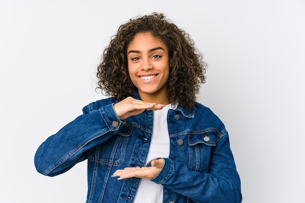 Jonge afrikaanse amerikaanse vrouwenholding iets met beide handen, productpresentatie.
