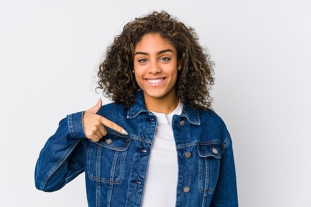 Jonge afrikaanse amerikaanse vrouwenpersoon die met de hand naar de ruimte van een overhemdskopie richt, trots en zelfverzekerd