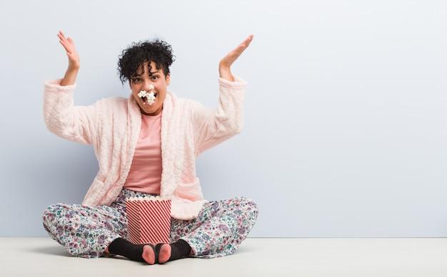Jonge afrikaanse amerikaanse vrouwenzitting die een popcorndoos houdt