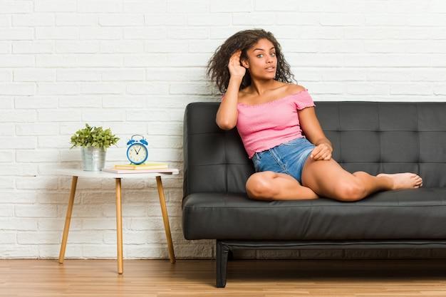 Jonge afrikaanse amerikaanse vrouwenzitting op de bank die aan het luisteren van een roddel probeert.