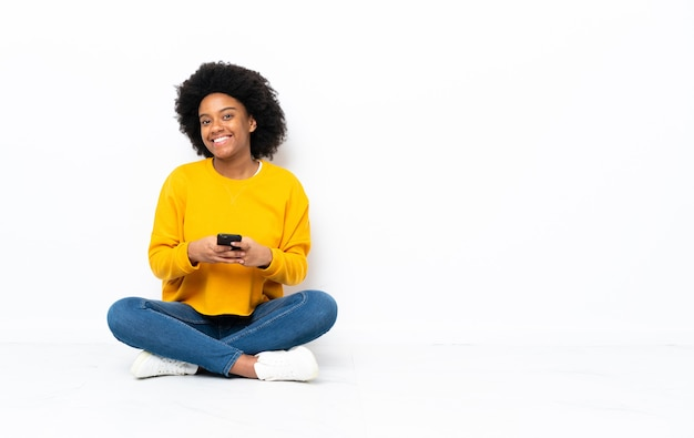 Jonge afrikaanse amerikaanse vrouwenzitting op de vloer die een bericht met mobiel verzendt