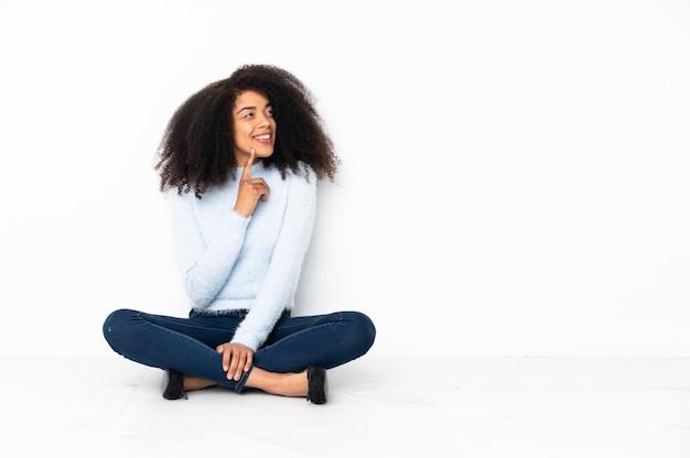 Jonge afrikaanse amerikaanse vrouwenzitting op de vloer die een idee denken terwijl omhoog het kijken