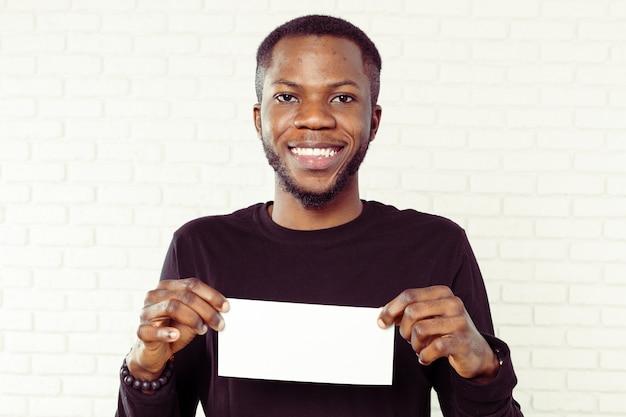 Jonge afrikaanse amerikaanse zakenman die lege kaart toont