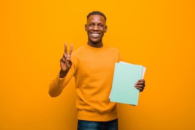 Jonge afrikaanse amerikaanse zwarte man tegen oranje muur met een boek