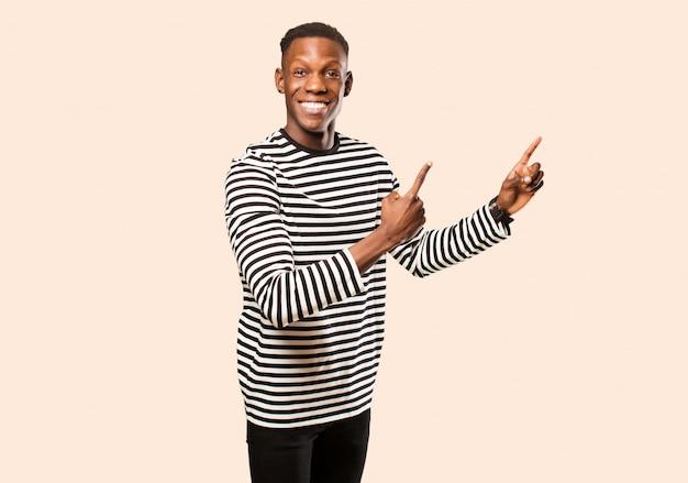 Jonge afrikaanse amerikaanse zwarte mens die gelukkig glimlacht en naar kant en omhoog wijst met beide handen die voorwerp in exemplaarruimte tegen beige muur tonen