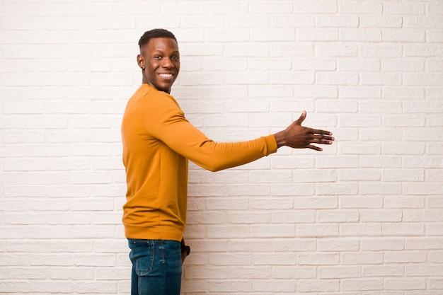 Jonge afrikaanse amerikaanse zwarte mens die, u begroet glimlacht en een handschok aanbiedt om een succesvolle overeenkomst, samenwerkingsconcept tegen bakstenen muur te sluiten