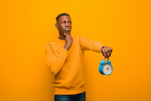 Jonge afrikaanse amerikaanse zwarte mens tegen oranje muur die een wekker houdt