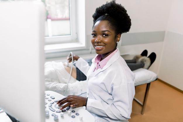 Jonge afrikaanse arts, camera kijken en glimlachen, terwijl het uitvoeren van echografie