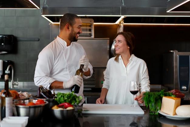 Jonge afrikaanse chef-kok kookt samen met blanke vriendin in de keuken
