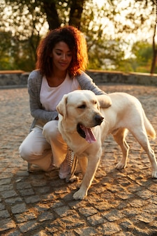 Jonge afrikaanse dame in vrijetijdskleding die en hond in park zitten koesteren