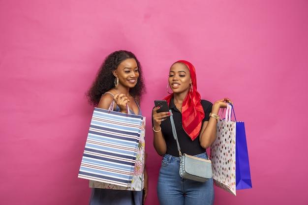 Jonge afrikaanse dames bekijken iets op een mobiele telefoon terwijl ze boodschappentassen dragen