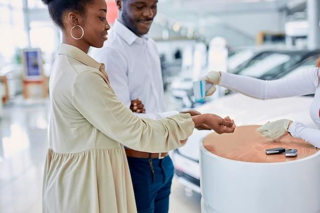 Jonge afrikaanse echtpaar wordt gecontroleerd op temperatuur in de dealer