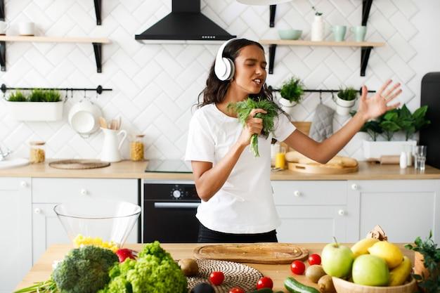 Jonge afrikaanse emotionele vrouw luistert naar muziek via een koptelefoon en houdt dille