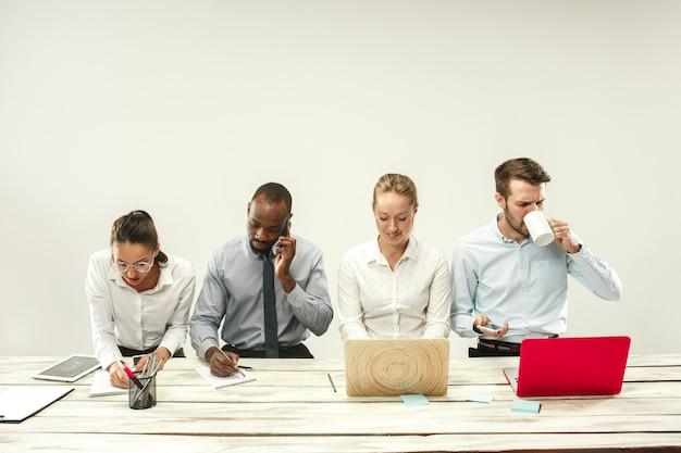 Jonge afrikaanse en blanke mannen en vrouwen die op kantoor zitten en op laptops werken. het bedrijf, emoties, team, teamwerk, werkplek, leiderschap, vergaderconcept. verschillende emoties van collega's