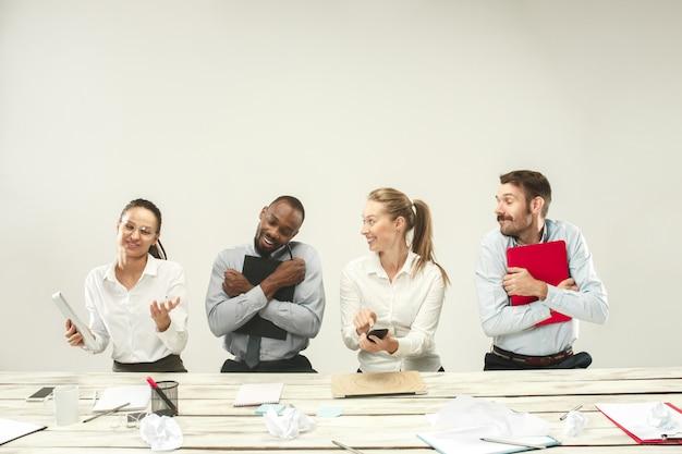 Jonge afrikaanse en kaukasische mannen en vrouwen die op kantoor zitten en aan laptops werken.