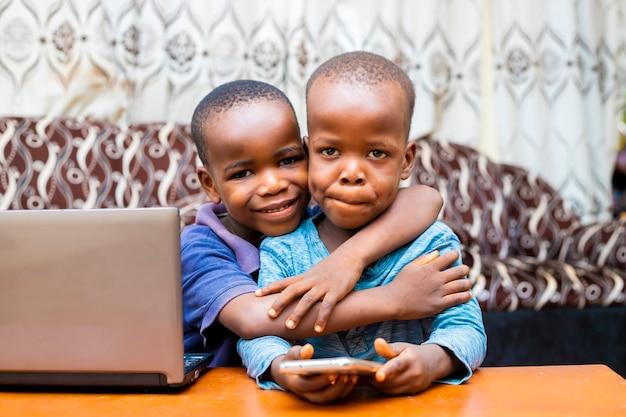 Jonge afrikaanse glimlachend houden elkaar met behulp van technologie kijken naar de camera weergegeven