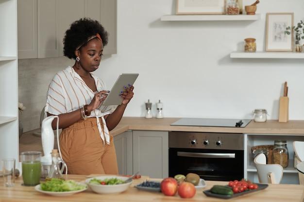 Jonge afrikaanse huisvrouw met tablet die online recepten doorbladert