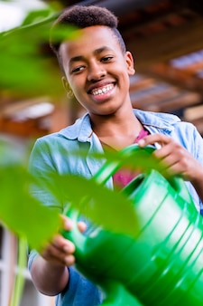 Jonge afrikaanse jongen het water geven installaties in tuin
