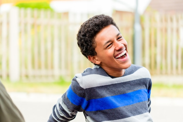 Jonge afrikaanse jongenszitting op vloer in tuin