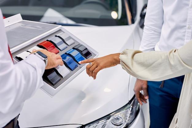 Jonge afrikaanse klanten kiezen de kleur van de auto bij de dealer
