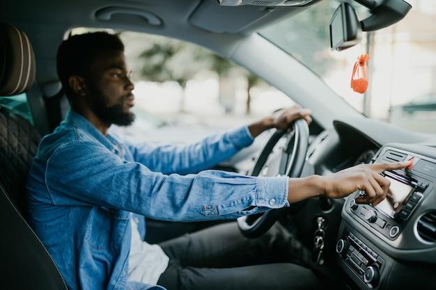 Jonge afrikaanse knappe man op noodknop drukken in de auto terwijl er iets met de auto gebeurde