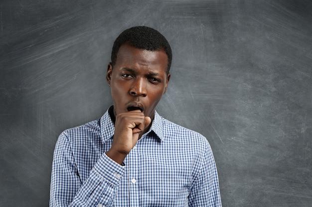 Jonge afrikaanse leraar die er moe en slaperig uitziet, geeuwt, zijn mond bedekt met, na een slapeloze nacht. zwarte student kijkt verveeld en ongeïnteresseerd tijdens wiskundelessen op de universiteit.