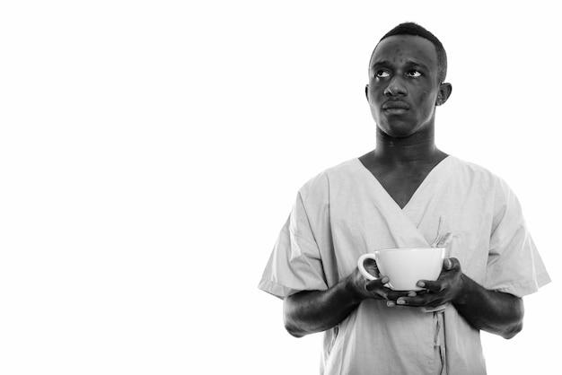 Jonge afrikaanse man als ziekenhuispatiënt geïsoleerd tegen witte muur in zwart en wit