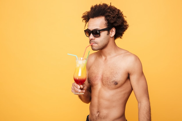 Jonge afrikaanse man cocktail drinken.