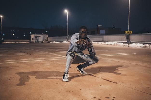 Jonge afrikaanse man dansen in parkeerplaats