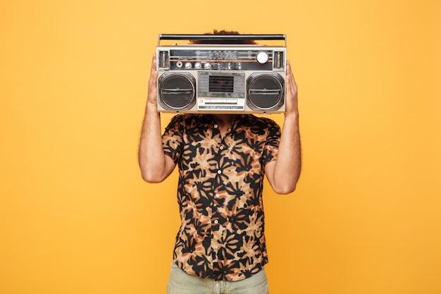 Jonge afrikaanse man die betrekking hebben op gezicht met tape recorder