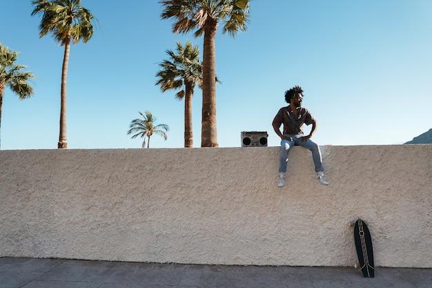 Jonge afrikaanse man die muziek luistert met vintage boombox-stereo met palmen op de achtergrond