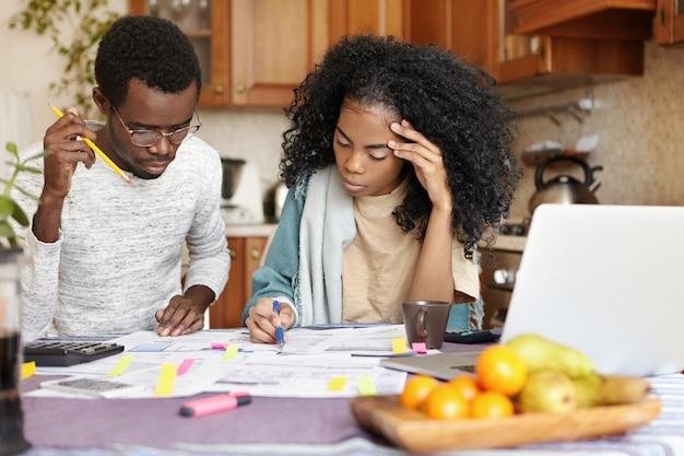 Jonge afrikaanse man en vrouw die papierwerk samen thuis doen, nieuwe aankoop plannen, gezinsuitgaven berekenen, zittend aan de keukentafel met laptop en rekenmachine. binnenlands budget en financiën