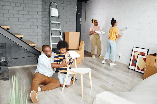 Jonge afrikaanse man en zijn schattige zoontje monteren een houten stoel terwijl ze op de grond zitten tegen twee vrouwtjes die de muur in witte kleur schilderen